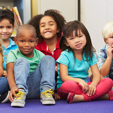A diverse group of young children seated on the ground
