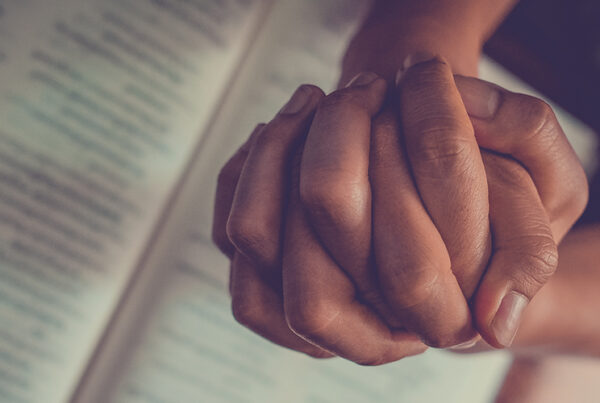 Hands clasped in prayer over an open Bible
