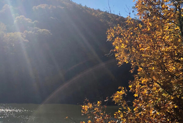 Sunbeams over a river with mountains in the background